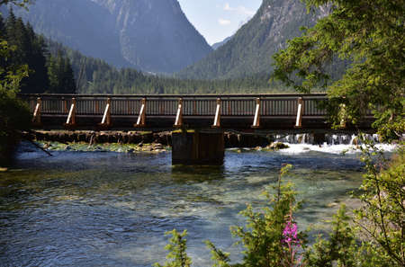 The wooden bridge that crosses the Rienza river out of Lake Dobbiaco Stock Photo