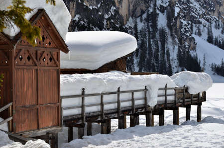 The old wooden structure of the boat rental on Lake Braies covered by a heavy snowfall Stock Photo
