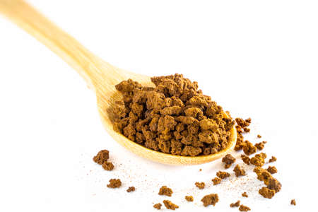 Instant coffee powder in a wooden spoon on a white background