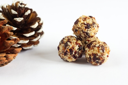 Photo of handmade vegan balls made from coconut, cranberries and nuts.