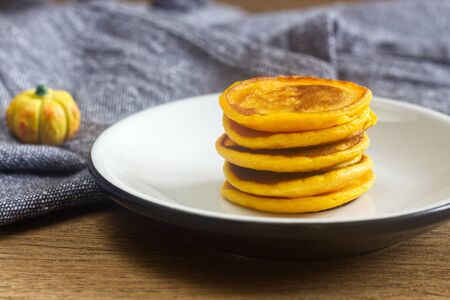 Photo of homemade pumpkin pancakes on the white plate.