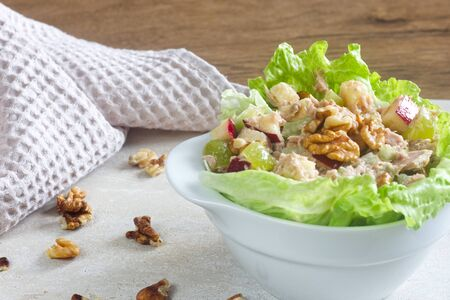 Photo of homemade waldorf salad made of celery, apples and walnuts, served on a bed of fresh leaf lettuce. Banco de Imagens