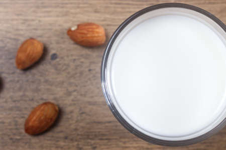 Photo of homemade almond milk with almond on a wooden table.