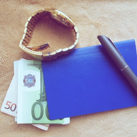 white collar crime: Watch,passport ,money and pen on yellow background Stock Photo