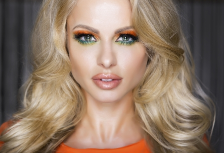 Beautiful blond woman with perfect makeup of eyes. Fashion model with curly hairstyle.