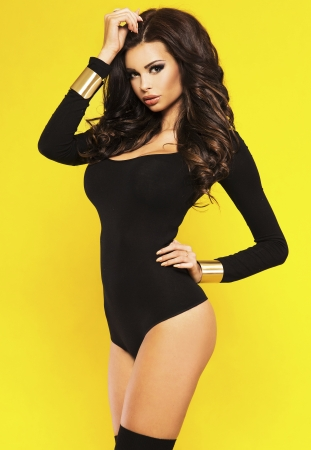 Attractive young brunette woman posing with long curly hair over yellow background, looking at camera.