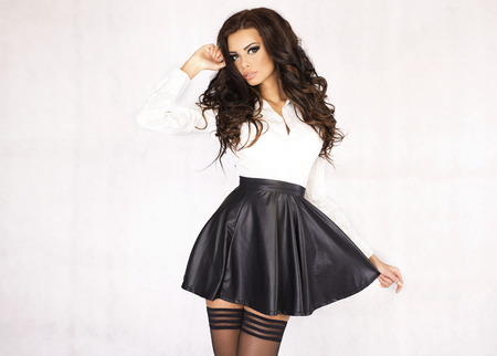 Fashionable young brunette woman posing wearing leather skirt and white shirt, looking at camera.