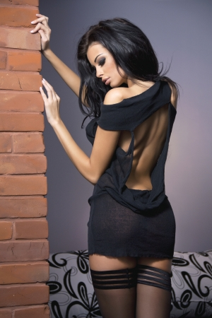 Sexy beautiful brunette woman posing in sensual clothes. Indoor shot. Фото со стока