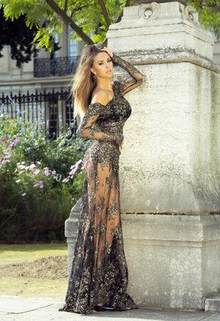 Beautiful brunette woman posing, wearing elegant dress, looking at camera. photo