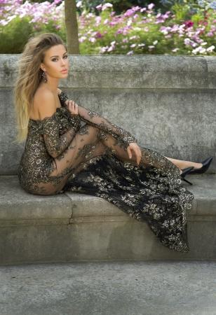 Elegant beautiful woman posing wearing gorgeous dress, looking at camera. photo
