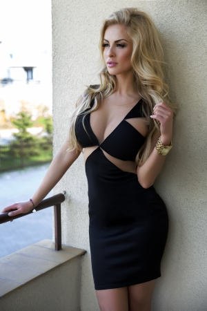 Elegant attractive blonde woman posing wearing black dress. Girl with long curly hair.