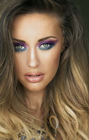 Beauty portrait of attractive young woman with colorful makeup looking at camera.