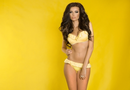 Beautiful brunette woman posing in sensual swimsuit over yellow . Studio shot. photo