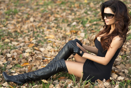 Fashionable young brunette woman posing in black dress and sunglasses. photo