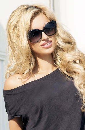 Portrait of a beautiful adult blonde woman with healthy long curly hair