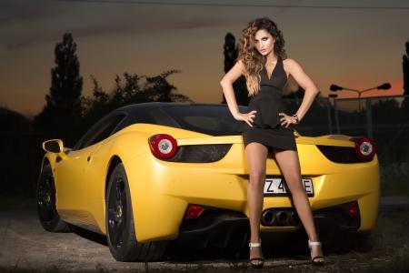 Beautiful brunette woman posing with sports car, wearing elegant dress, looking at camera.