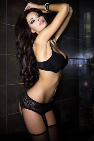 Beautiful brunette woman posing inblack sexy lingerie with closed eyes.