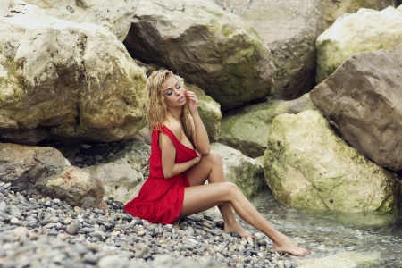Attractive young blondte beauty posing on rocky coast in elegant red dress. Wet hair. Standard-Bild