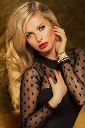 Portrait of elegant blonde beauty looking at camera. Beautiful woman posing with red lips and curly long hair. Stock Photo