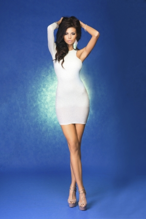 Fashion photo of sexy brunette woman wearing elegant dress, posing, looking at camera.