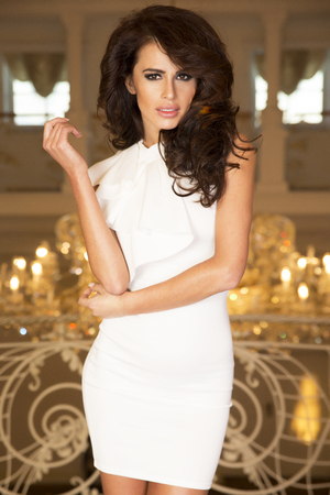 Elegant young brunette woman posing in fashionable white dress, looking at camera.