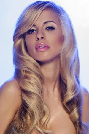 plan éloigné: Portrait de la belle jeune fille blonde. Studio, coup. Femme aux longs cheveux bouclés et maquillage parfait.