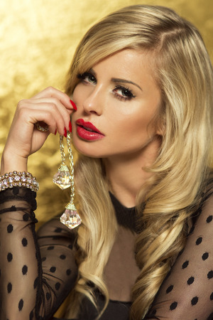 Portrait of sensual blonde beauty with red lips looking at camera.