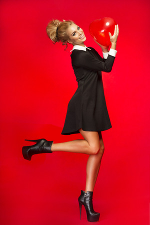 Sensual blonde fashionable woman posing wearing black dress, smiling, looking at camera  Studio shot  Red background  photo