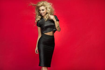 Fashionable blonde young woman posing, looking away. Studio shot. Standard-Bild
