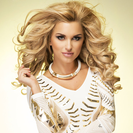 Fashionable blonde young woman posing, looking at camera. Studio shot.