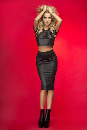 Sexy beautiful blonde woman posing in fashionable clothes, studio shot. Girl looking at camera. Red background.