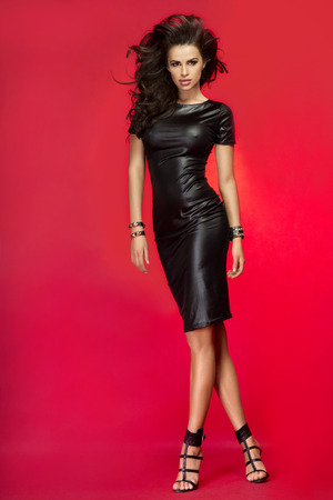 sexual pleasure: Sexy beautiful brunette woman posing in leather black dress. Girl with long curly healthy hair. Studio shot. Stock Photo