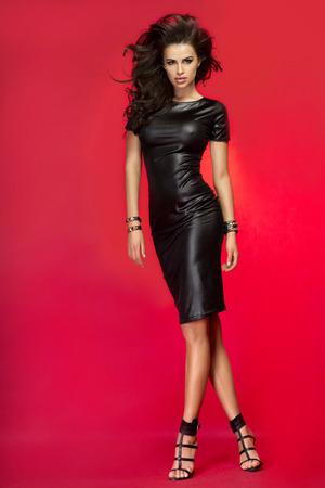 femme brune: Sexy belle femme brune posant en robe en cuir noir. Fille aux longs cheveux boucl�s saine. Studio photo.