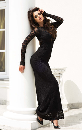 Sensual brunette beautiful woman posing in long black elegant dress. Stock Photo