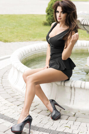 fine legs: Elegant beautiful brunette lady posing outdoor, wearing black mini dress. Stock Photo