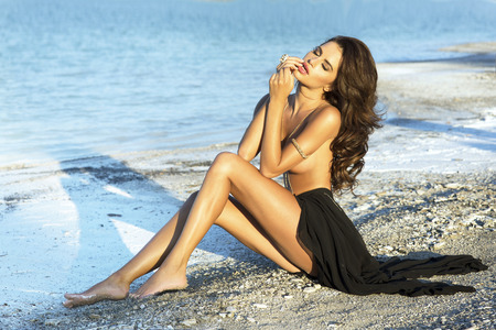 Sensual brunette beautiful woman posing on the beach, sunny day. photo