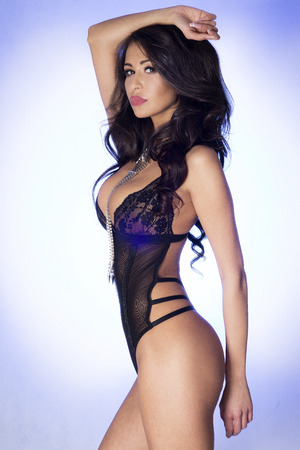Sexy brunette woman posing wearing sensual lingerie, looking at camera