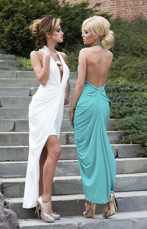 nearness: Two elegant beautiful woman posing outdoor wearing fashionable maxi dress.