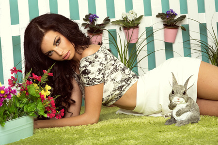Artistic portrait of beautiful brunette woman in garden , spring. Standard-Bild
