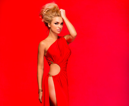 Fashionable young beautiful blonde woman posing in red elegant dress. Sexy look.