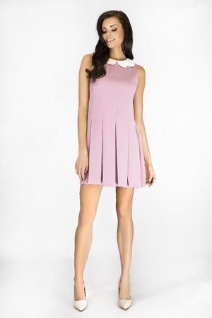 Fashionable young pretty girl posing in dress. Studio shot. Full body. Brunette elegant lady.