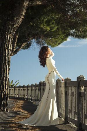maxi dress: Elegant brunette woman standing outdoor in beautiful white maxi dress, looking away. Stock Photo