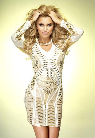 Fashionable sexy blonde woman posing in studio, looking at camera. Girl wearing luxury dress Standard-Bild
