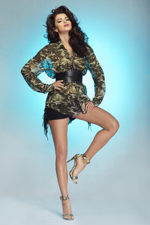 long legs: Sexy brunette woman posing in fashionable clothes over blue studio background