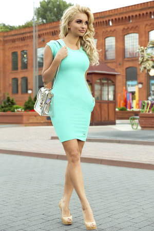 Attractive blonde smiling woman posing outdoor in sunny day