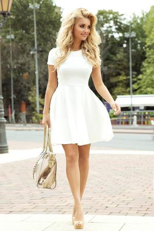 Fashionable beautiful blonde woman posing outdoor. Smiling girl.