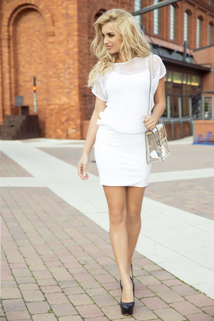 Elegant fashionable beautiful blonde woman posing outdoor in casual clothes. Girl with long curly hair.