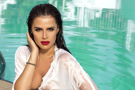 Sexy brunette woman relaxing in swimming pool, looking at amera. Beauty portrait.