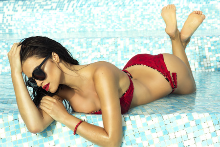 Sexy beautiful brunette woman with perfect body lying in swimming pool, sunbathing.
