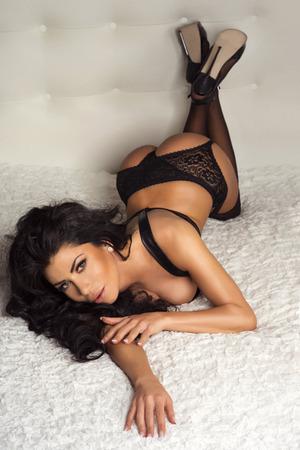 Sexy Brünette Frau im Bett liegend, tragen modische sinnliche schwarzen Dessous, Blick in die Kamera. Standard-Bild - 32962608